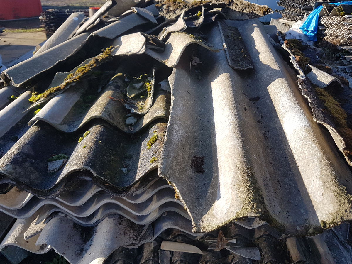 A pile of broken corrugated asbestos cement sheets